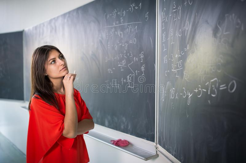 Pretty, young college student writing on the chalkboard. /blackboard during a math class royalty free stock images