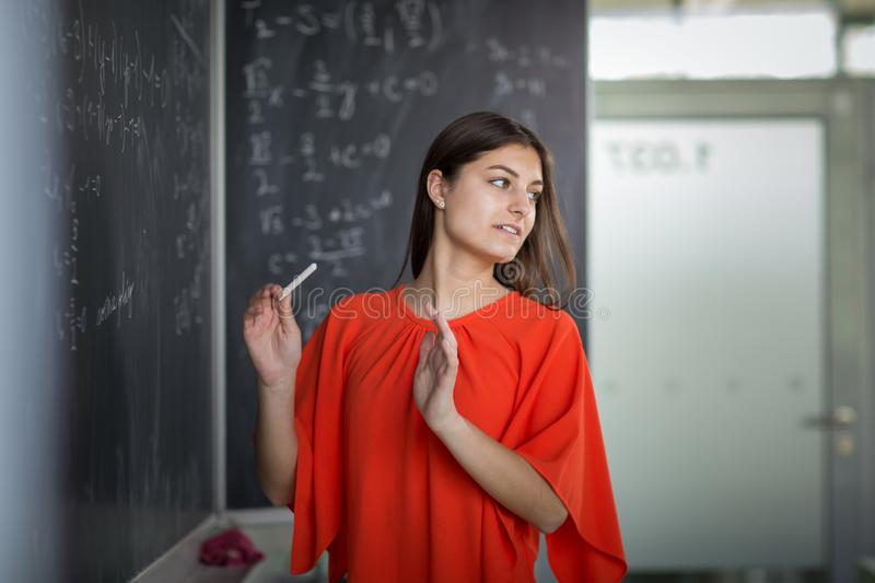 Pretty, young college student writing on the chalkboard. /blackboard during a math class stock photography