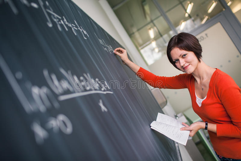 Pretty, young college student writing on the chalkboard. /blackboard during a math class color toned image stock photography