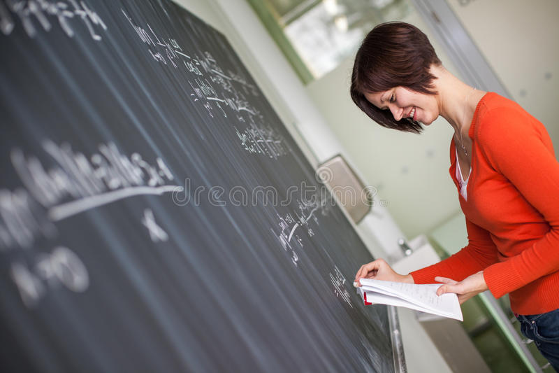 Pretty, young college student writing on the chalkboard. /blackboard during a math class color toned image royalty free stock images