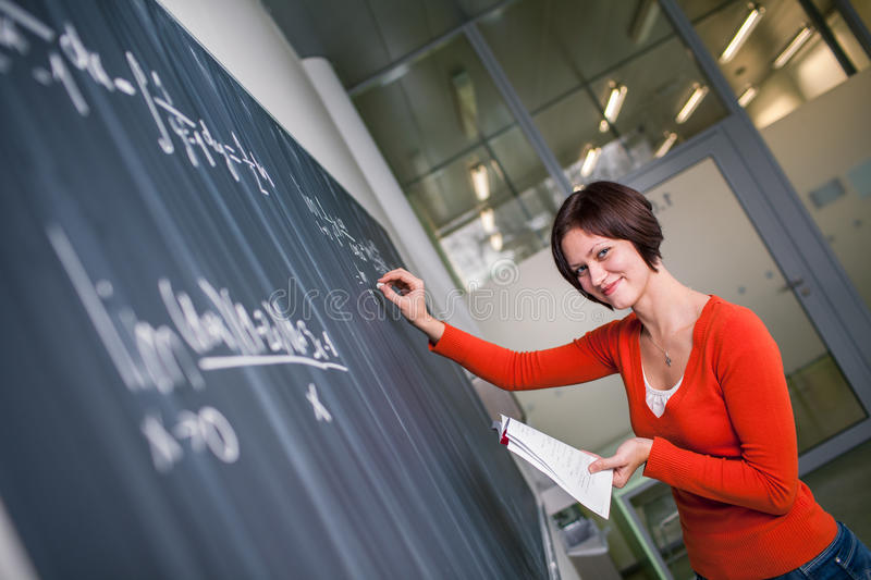 Pretty, young college student writing on the chalkboard. /blackboard during a math class color toned image stock images