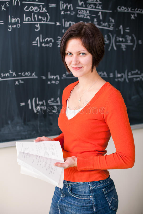 Pretty, young college student writing on the chalkboard. /blackboard during a math class (color toned image royalty free stock images