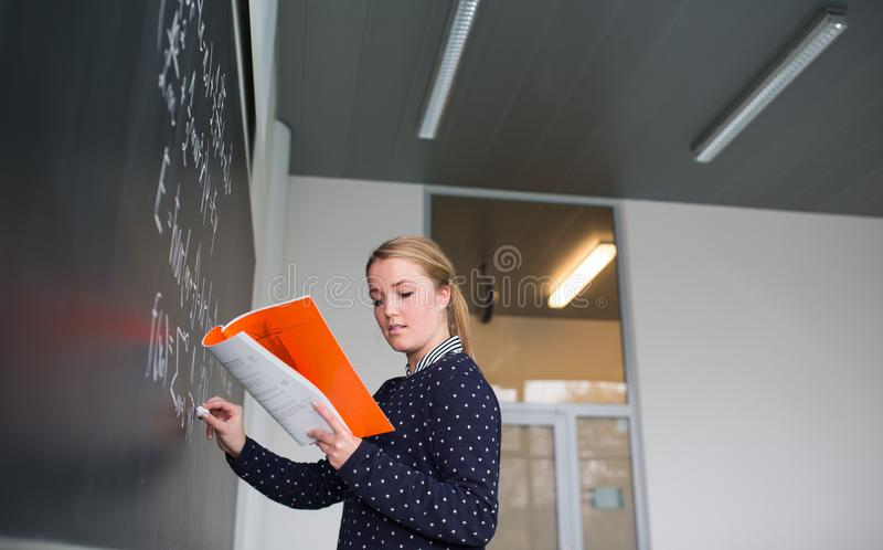 Pretty, young college student writing on the chalkboard. /blackboard during a math class colort toned image; shallow DOF stock images