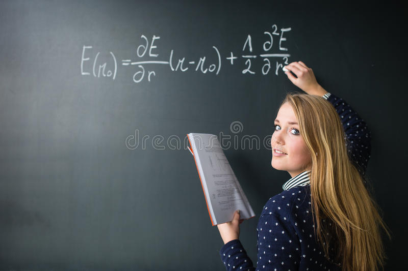 Pretty, young college student writing on the chalkboard. /blackboard during a math class colort toned image; shallow DOF stock photography