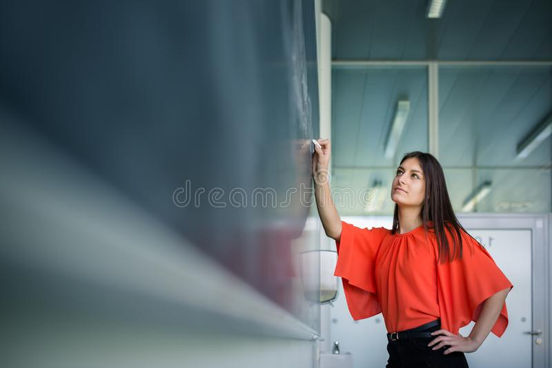 Pretty, young college student writing on the chalkboard/blackboard. During a math class stock photography