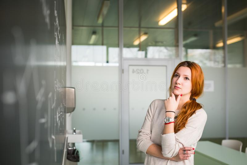 Pretty young college student writing on the chalkboard/blackboard. During a math class royalty free stock image