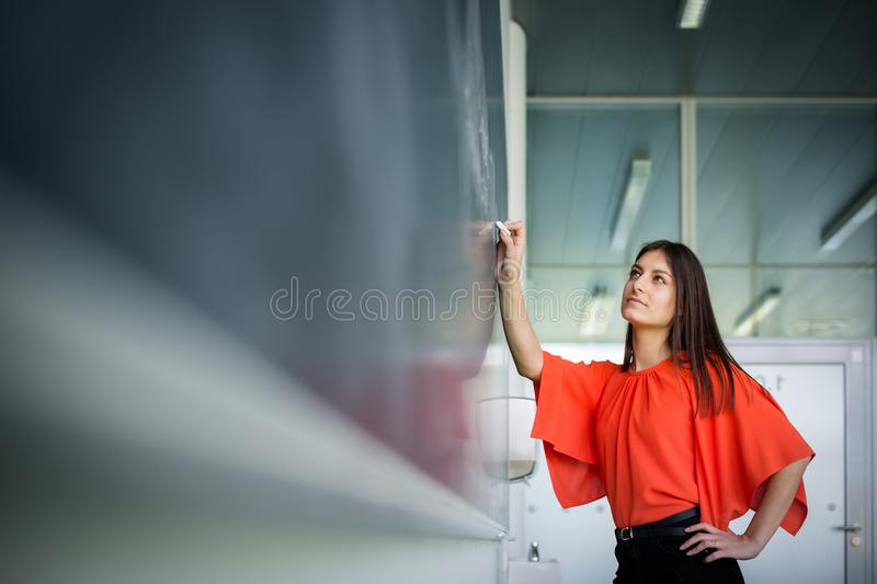 Pretty, young college student writing on the chalkboard royalty free stock photo