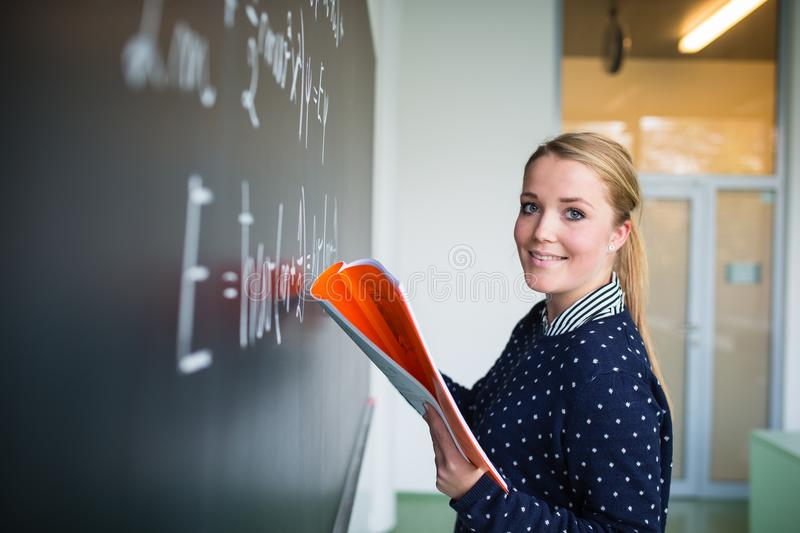 Pretty, young college student writing on the chalkboard. /blackboard during a math class colort toned image; shallow DOF royalty free stock photo