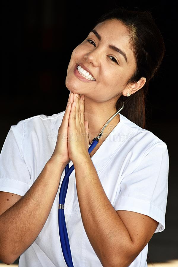 Appreciative Attractive Nurse Wearing Scrubs. A pretty young Colombian adult female stock images