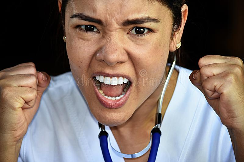 Mad Latina Female Nurse Medical Professional Wearing Scrubs. A pretty young Colombian adult female stock photography
