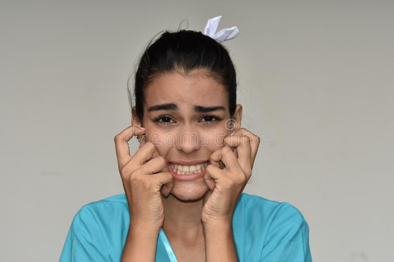 Hispanic Female Nurse Under Stress. A pretty young Colombian teen girl royalty free stock images