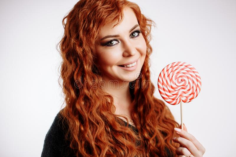 Pretty young curly redhead woman holding big sweet lollipop and smiling stock photography