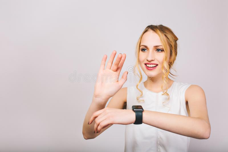 Pretty young fair-haired lady waving with her hands and posing with smile isolated on white background. Charming girl royalty free stock image