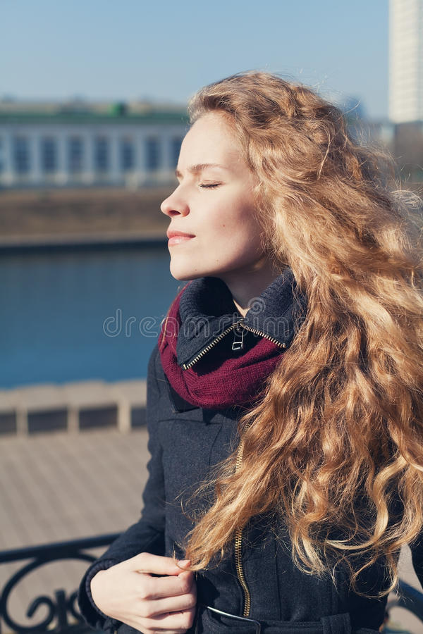Pretty young fashion woman with long curly hair enjoying the spring sun with eyes closed near the river. In the street background, meditation or relaxation stock photos