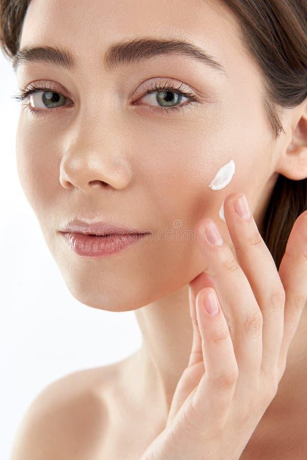 Pretty young female applying cream on cheek stock photography