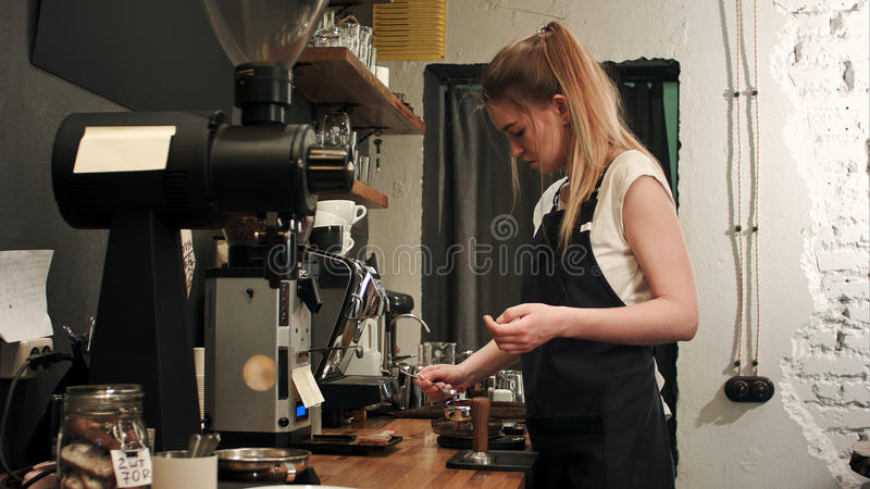 Pretty young female barista weighing coffee grains on a scale before brewing a cup of coffee. Professional shot in 4K resolution. 089. You can use it e.g. in stock photos