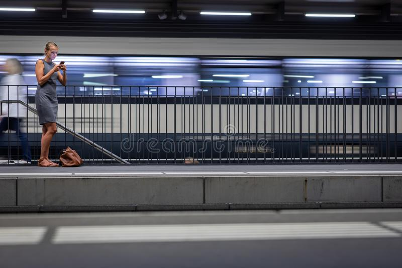 Pretty, young female commuter, waiting for her train royalty free stock image