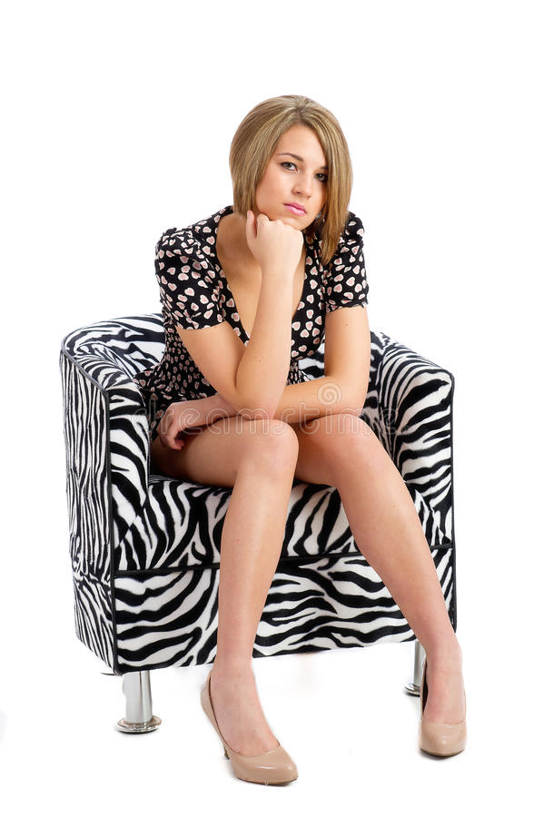 Pretty young female isolated posing in chair stock photos