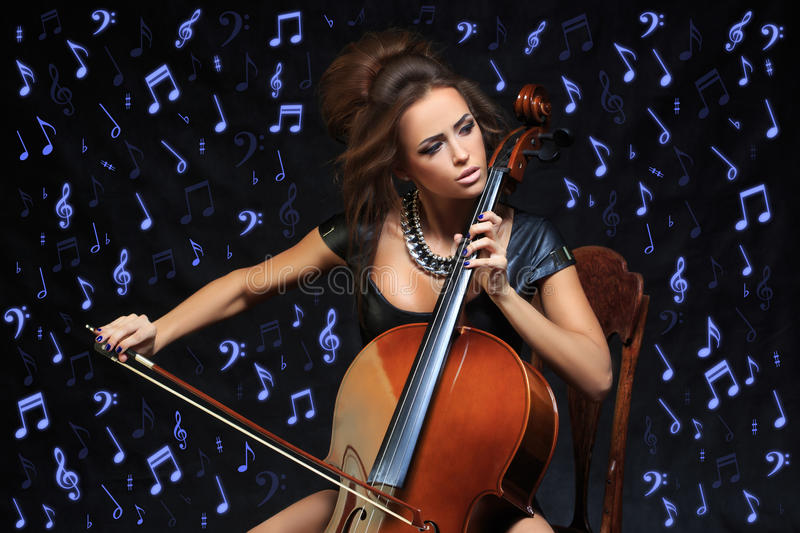 Pretty young female musician playing the cello. At a classical recital concentrating on her notes in the darkness, close up view royalty free stock photo