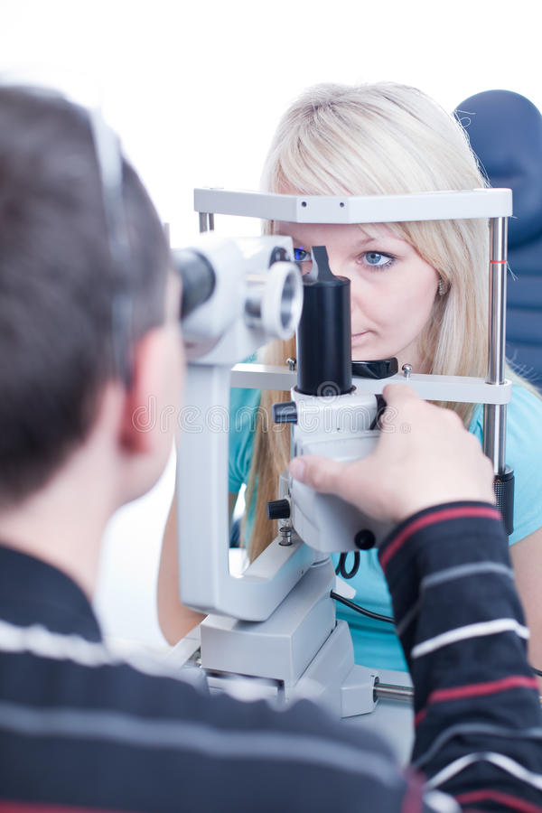 Pretty young female patient. Optometry concept - pretty young female patient having her eyes examined by an eye doctor stock images