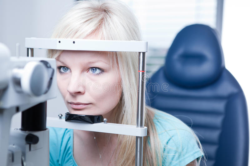 Pretty young female patient. Optometry concept - pretty young female patient having her eyes examined by an eye doctor royalty free stock images