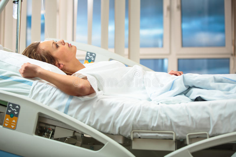 Pretty, young, female patient in a modern hospital room royalty free stock photography