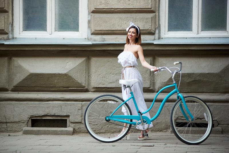 Pretty young female posing with blue bike in front of old historical building stock photos
