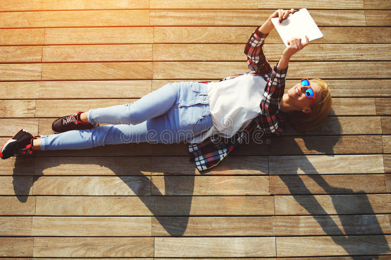 Pretty young female student relaxing in the day and taking self-ie with digital tablet camera stock photography