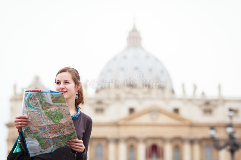 Pretty young female tourist studying a map