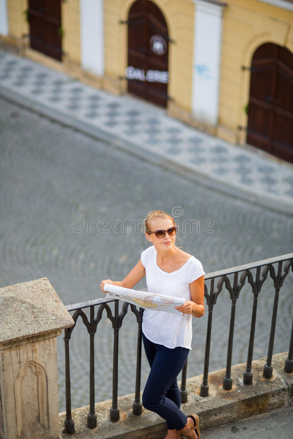 Pretty young female tourist studying a map. Enjoying discovering a new city, looking excited (shallow DOF; color toned image royalty free stock photos