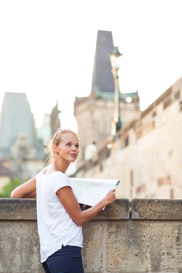 Pretty young female tourist studying a map. Enjoying discovering a new city, looking excited (shallow DOF; color toned image royalty free stock photography