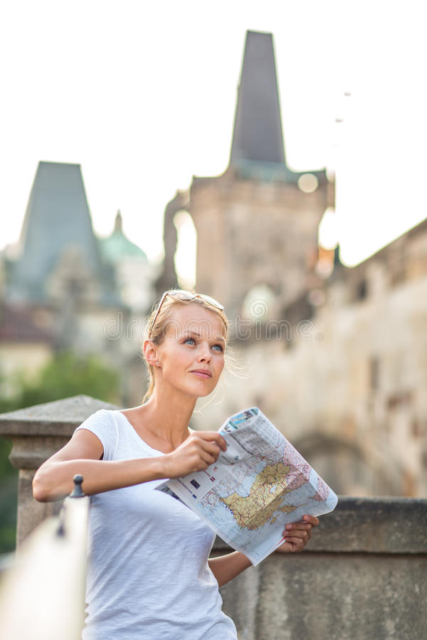 Pretty young female tourist studying a map. Enjoying discovering a new city, looking excited (shallow DOF; color toned image royalty free stock photo