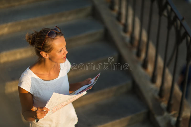 Pretty young female tourist studying a map. Enjoying discovering a new city, looking excited (shallow DOF; color toned image stock photos