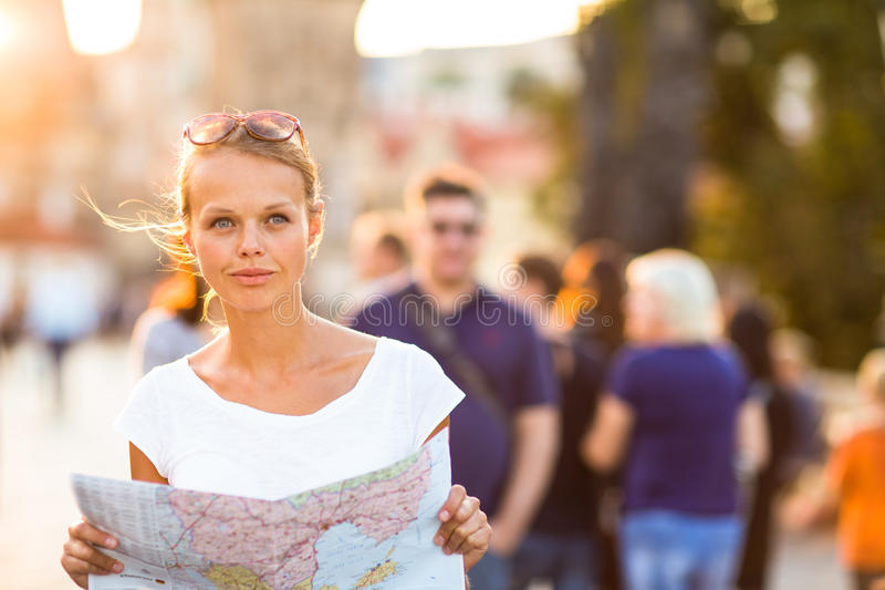 Pretty young female tourist studying a map. Enjoying discovering a new city, looking excited (shallow DOF; color toned image royalty free stock image