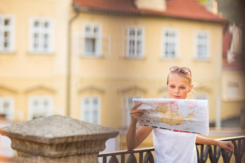 Pretty young female tourist studying a map. Enjoying discovering a new city, looking excited (shallow DOF; color toned image stock photo