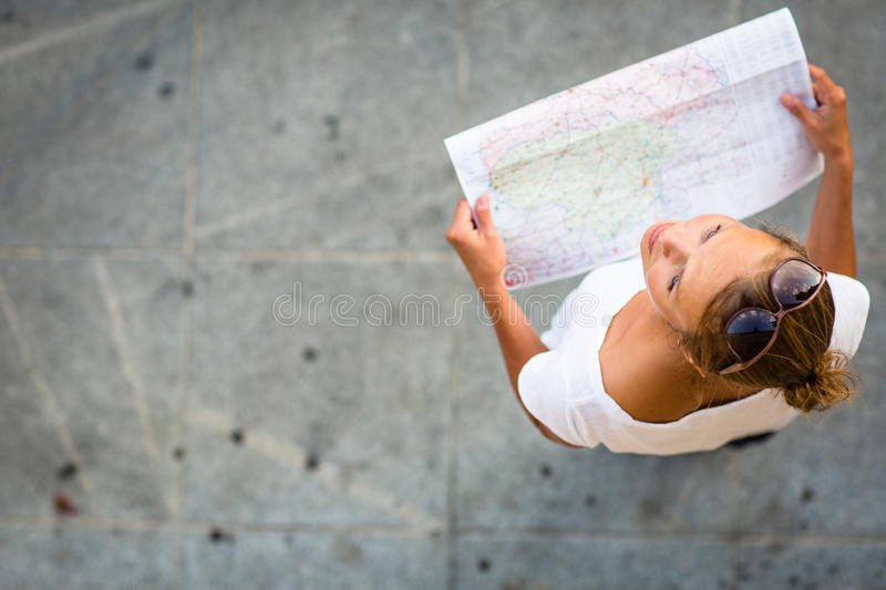 Pretty young female tourist studying a map. Enjoying discovering a new city, looking excited (shallow DOF; color toned image royalty free stock images