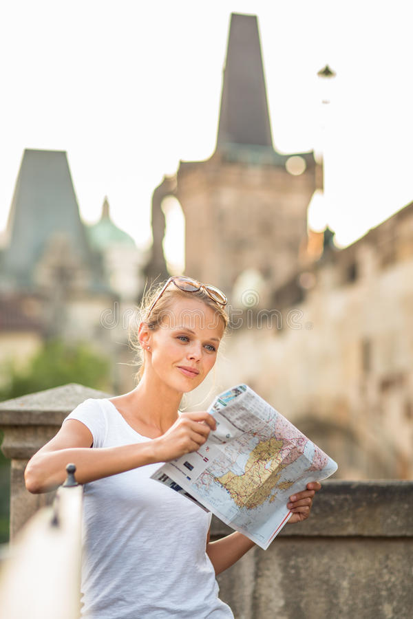 Pretty young female tourist studying a map. Enjoying discovering a new city, looking excited (shallow DOF; color toned image stock images