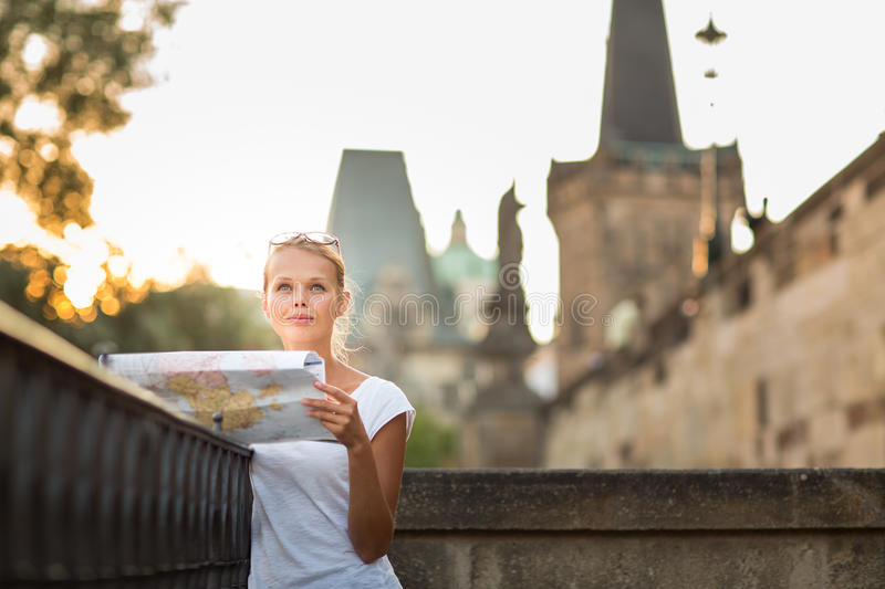 Pretty young female tourist studying a map. Enjoying discovering a new city, looking excited shallow DOF; color toned image stock images