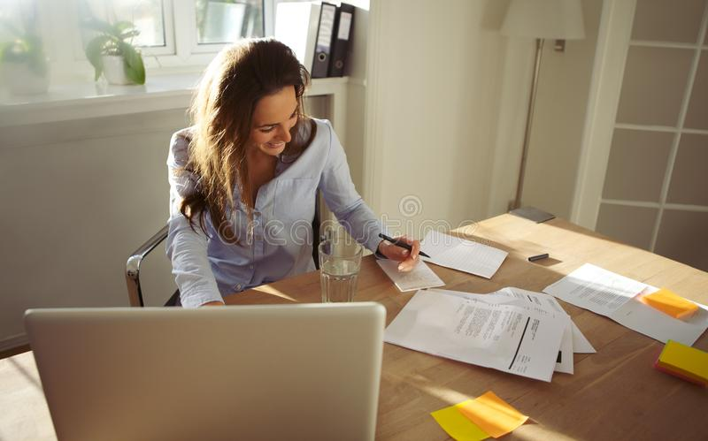Pretty young female writing notes smiling stock photography