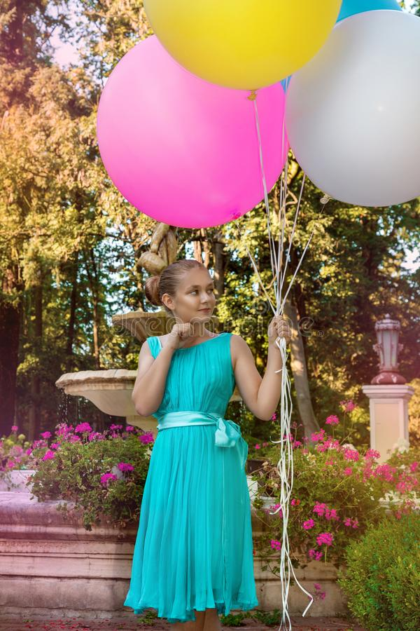 Pretty young girl with big colorful balloons walking in the park near the town - image stock photography