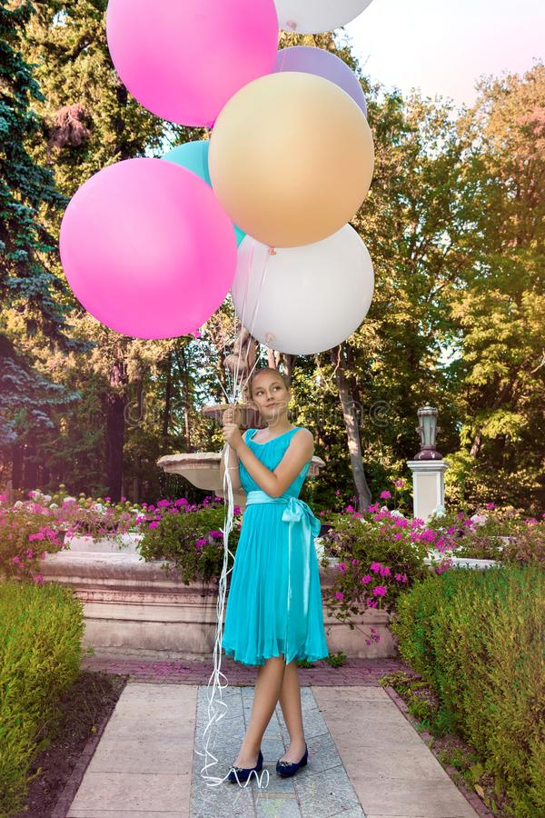 Pretty young girl with big colorful balloons walking in the park near the town - image stock image