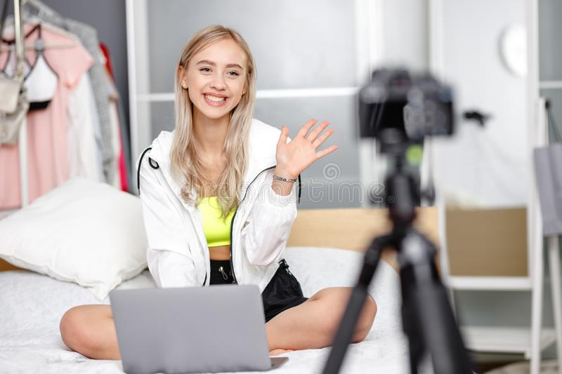 Pretty young girl blogger dressed in fashionable clothes is being filmed for her blog video sitting on the bed with a stock photos