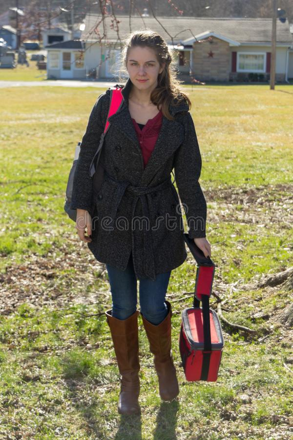 Pretty young girl coming home from school in boots stock image