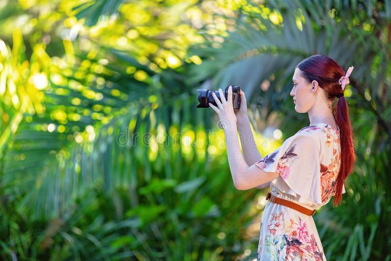 Young Woman Photographer Taking Images In A Garden royalty free stock images