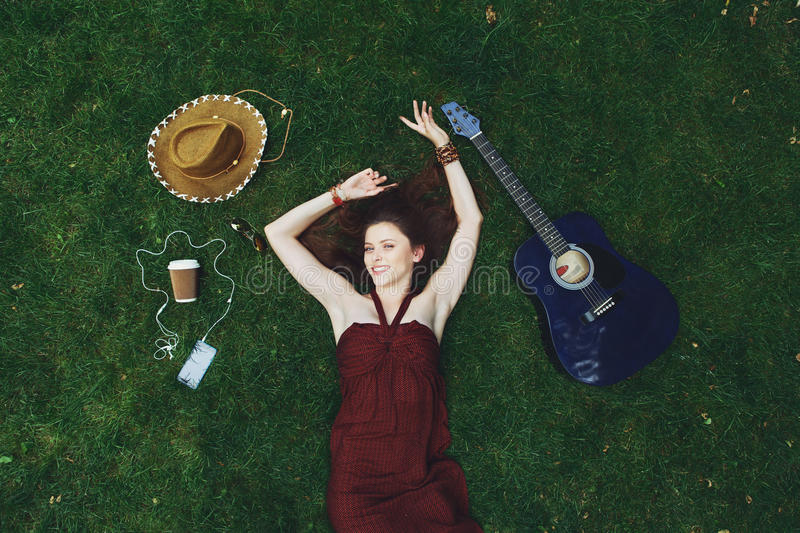 Pretty young girl with guitar lying on grass royalty free stock photo