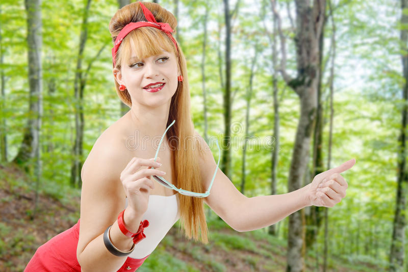 Pretty young girl hitchhiking in the forest. Pretty young blonde girl hitchhiking in the forest stock photography