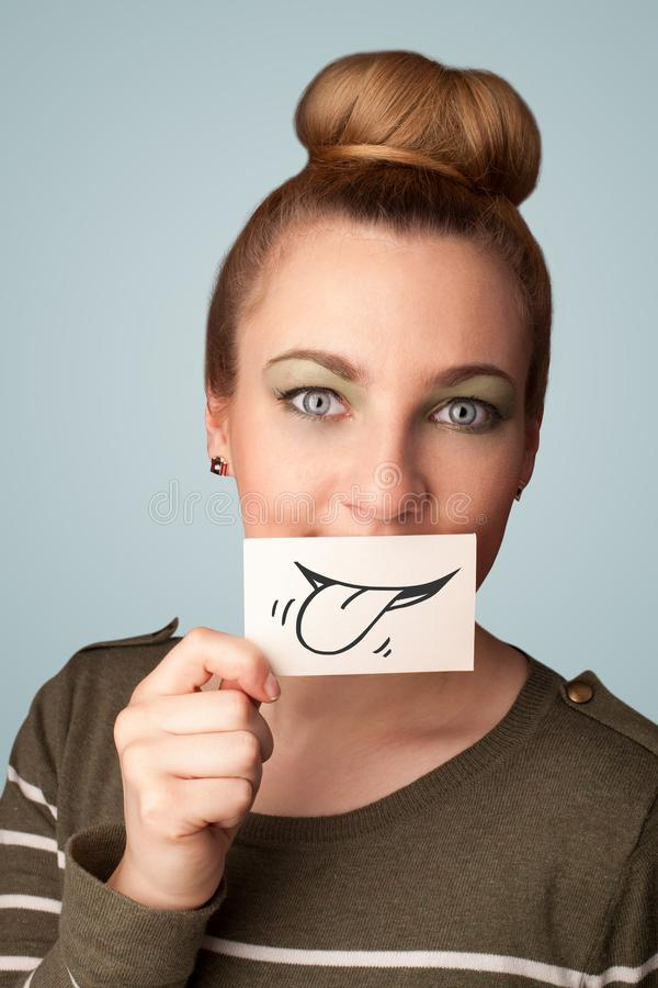 Pretty young girl holding white card with smile drawing. On gradient background royalty free stock images