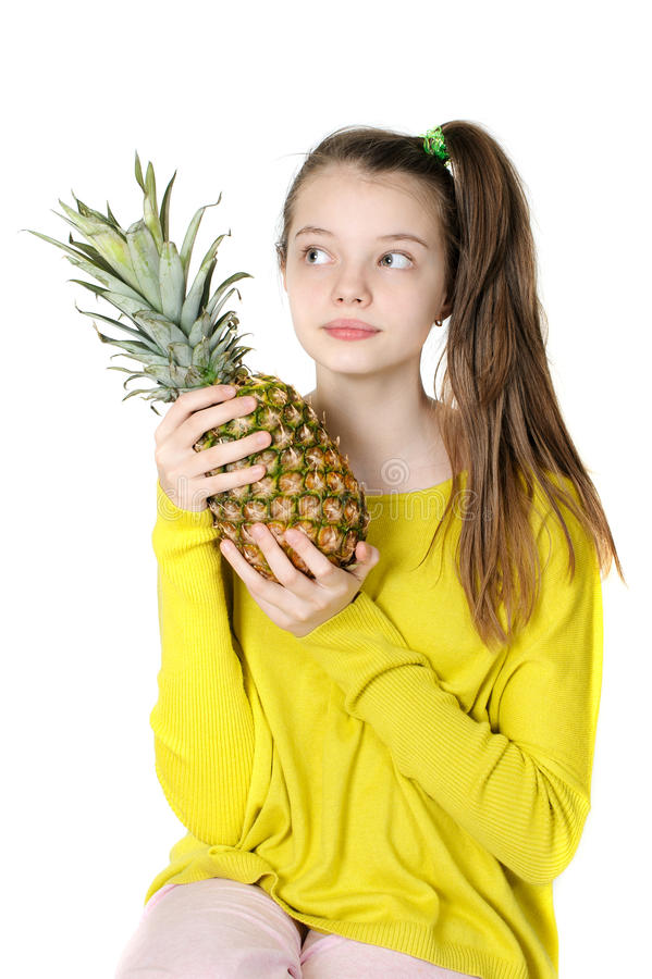 Pretty young girl looks up and holds a large pineapple. royalty free stock image