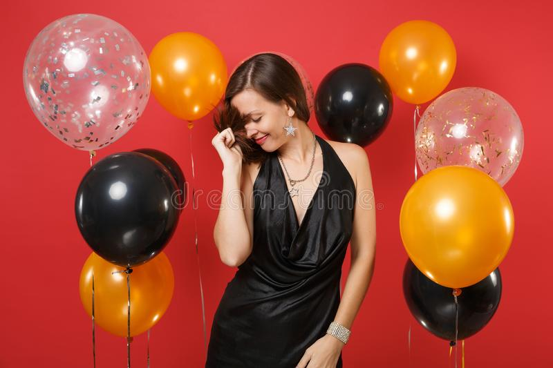 Pretty young girl with lowered head in black dress celebrating holding her hair on bright red background air balloons royalty free stock photography