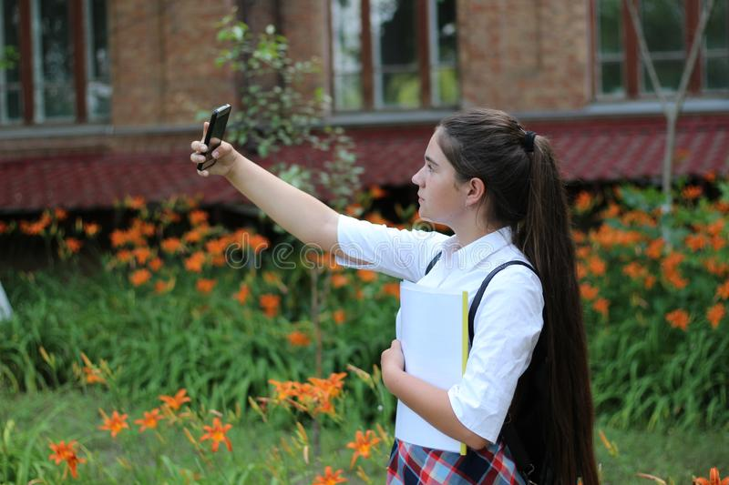Girl- schoolgirl with long hair in school uniform makes selfie stock photography